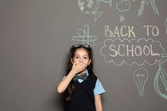 Little child in uniform near drawings with text. BACK TO SCHOOL on grey background royalty free stock images