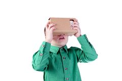 Little child uses virtual reality (VR cardboard)  on white background Royalty Free Stock Image