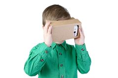 Little child uses virtual reality (VR cardboard)  on white background Royalty Free Stock Images
