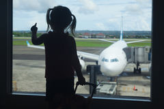 Little child waiting for boarding to flight in airport terminal. Silhouette of little baby girl waiting boarding to her flight in airport transit hall and Stock Photography