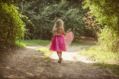 Little child walking in the rural foothpath back view. Little child with long blond hair dressed in pink dress walking in the rural path in the forest  back to Stock Images