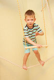 Little child walking on a tightrope in the sports complex. Royalty Free Stock Images