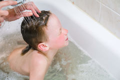 Little child is washing her hair in bath Stock Photos