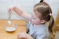 Little girl  eats useful porridge. Little child is watching his porridge carefully stock images