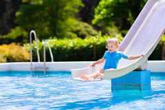 Little child on water slide in swimming pool Royalty Free Stock Image