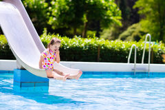 Little child on water slide in swimming pool Royalty Free Stock Images