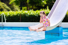 Little child on water slide in swimming pool Stock Photo
