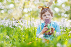 Little child wearing Easter bunny ears and eating chocolate at s. Cute happy little child wearing Easter bunny ears at spring green grass and blooming apple Stock Photo