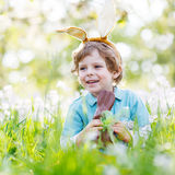 Little child wearing Easter bunny ears and eating chocolate at s Royalty Free Stock Photo
