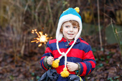 Little child in winter clothes holding burning sparkler. Funny little boy in winter clothes holding burning sparkler on New Year's Eve. Safe fireworks for kids Stock Photo