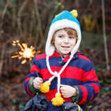 Little child in winter clothes holding burning sparkler. Funny little boy in winter clothes holding burning sparkler on New Year's Eve. Safe fireworks for kids Royalty Free Stock Image