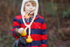 Little child in winter clothes holding burning sparkler Royalty Free Stock Images