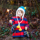 Little child in winter clothes holding burning sparkler. On New Year's Eve. Safe fireworks for kids concept. Happy kid boy outdoors Stock Images