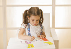 Little child writing letter A. Learning to write. Little girl writing alphabet in a copy book at a desk. Learn Study Education School Knowledge Concept Royalty Free Stock Photo