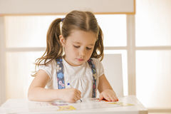 Little child writing letter A. Learning to write. Little girl writing alphabet in a copy book at a desk. Learn Study Education School Knowledge Concept Royalty Free Stock Images