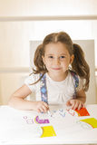 Little child writing letter A. Learning to write. Little girl writing alphabet in a copy book at a desk. Learn Study Education School Knowledge Concept Stock Images