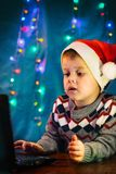 Little child writing letter to Santa Claus on laptop computer. Little boy with santa hat. stock photography