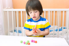 Little child (2 years) modelling playdough balls at home Stock Photo