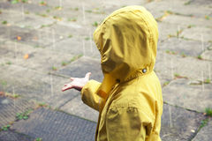 Little child in yellow raincoat playing with raindrops Stock Photography