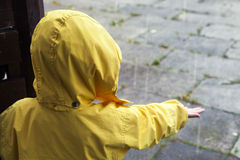 Little child in yellow raincoat playing with water drops Royalty Free Stock Photo