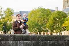 Little child and young father in autumn city Stock Photos