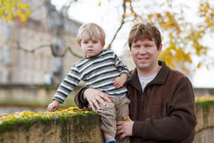 Little child and young father in autumn city Stock Images