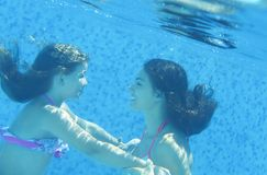Little child and young woman underwater in the swimming pool Royalty Free Stock Photos