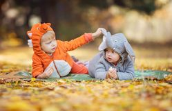 Little children in animal costumes playing in autumn forest Royalty Free Stock Photo
