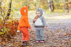 Little children in animal costumes playing in autumn forest Stock Images