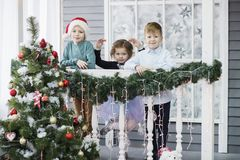 Little children In anticipation of new year and Christmas. Three little Kids are having fun and playing near Christmas tree royalty free stock photography