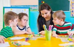 Little children at applique lesson. Cute little children having applique lesson at kindergarten Royalty Free Stock Photography