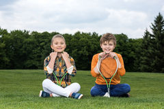 Little children with badminton racquets sitting on grass and smiling at camera. Adorable little children with badminton racquets sitting on grass and smiling at royalty free stock photos