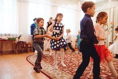 Little children in beautiful outfits celebrate feast of spring in kindergarten. Moscow, Russia - March 8, 2019: Little children in beautiful outfits celebrate royalty free stock photo
