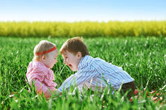 Little children boy and girl play on green grass Stock Images
