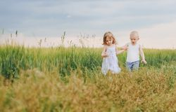 Children friendship love hands escape nature spring. Little children boy and girl running along forward the path the field hold on to the hand on nature Royalty Free Stock Image