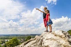 Little children boy and girl standing on mountain rock and looki Stock Photos