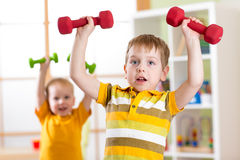 Little children boys exercising with dumbbells at home. Healthy life, sportive kids. Royalty Free Stock Images