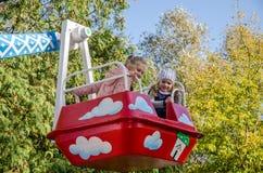 LVIV, UKRAINE - OCTOBER 2017: Little children, charming girls girlfriends ride in an amusement park on a swing stock photography