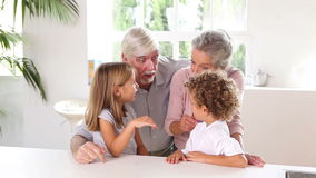 Little children chatting with grandparents Stock Image