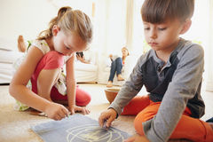 Little children drawing in living room at home Stock Photos