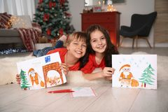 Little children with drawings and letter to Santa at home. Christmas celebration stock images
