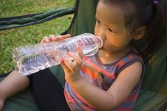 Little children drinking water from bottle in green park stock photography