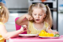Little children eating food at daycare Stock Image