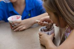 Little children eating ice-cream. Little brother and sister eating ice-cream in a cafe outdoors Stock Images