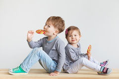 Little children eating lollipops Stock Images