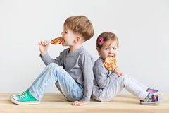 Little children eating lollipops Stock Photography