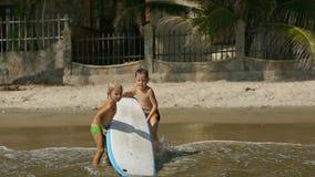 Little children enjoying sea surfboarding on summer vacation. Happy smiling adorable little children enjoying blue sea surfboarding on surfboard on summer stock video footage