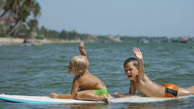 Little children enjoying sea surfboarding and waving hands in slow motion stock footage