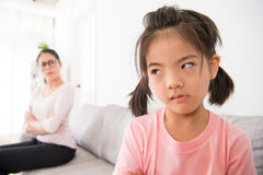 Little children girl feeling unhappy and angry. When her mother told her to write homework on the vacation at home with blur seriously mother background Royalty Free Stock Photo