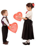 Little children give each other red balloons stock images